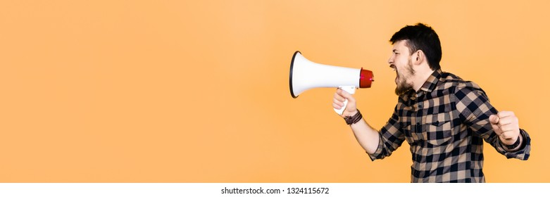 bearded man in shirt shouts into megaphone, panoramic image