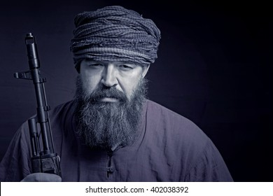 A bearded man in a shirt and a turban with arms squinting looks ahead. Toned