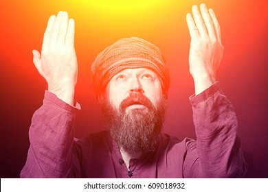 A bearded man in a shirt and a turban in a posture of prayer put his hands up to the light on a red background. Toned