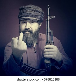 A bearded man in a  shirt and a turban with a rifle in hand looking forward to showing the middle finger. Toned