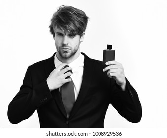 Bearded man, short beard. Caucasian stylish business man with moustache in elegant black suit and red tie posing with perfumes in studio isolated on white background