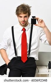 Bearded man, short beard. Caucasian stylish man posing with perfume in shirt and suspenders in studio isolated on white background