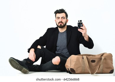 Bearded man, short beard. Caucasian hipster with moustache in sunglasses, leaning on stylish bag, holding perfume bottle, wearing black jacket and ripped jeans, isolated on white background