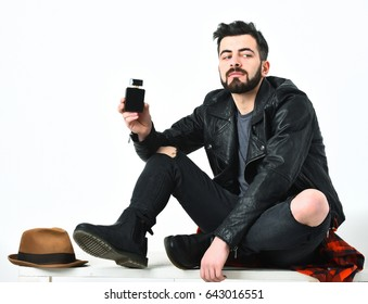 Bearded man, short beard. Caucasian serious hipster with moustache holding perfume bottle, wearing black leather jacket, checkered red shirt and ripped jeans isolated on white background