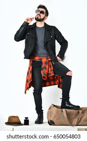Bearded man, short beard. Caucasian hipster with moustache smoking cigarette in sunglasses, black leather jacket, checkered red shirt and jeans isolated on white background, lookbook concept