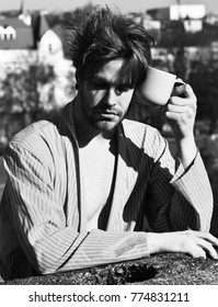 Bearded man, short beard. Caucasian sleepy macho with moustache and ruffled hair in blue striped pajamas holding cup or mug in roof on blurred city background, morning coffee concept