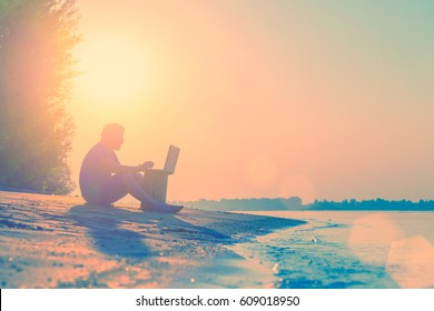 Bearded man in shorts sitting on a sandy beach near water and working at a laptop. Toned