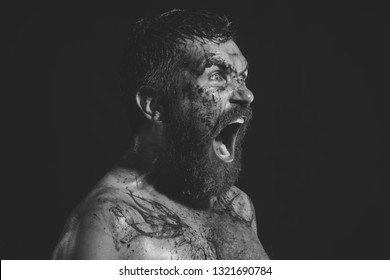 Bearded man shout with horror on brutal face. Hipster with bloody beard, tattoo on chest on black background. Halloween holidays celebration. Magic, enchantment, witchcraft. Wizard, sorcerer, warlock.