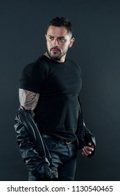 Bearded man show tattoo on strong arm. Tattooed man in tshirt and leather jacket. Fashion macho with beard on unshaven face. Masculinity and strength. Fashion style and trend.