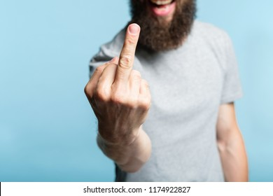 bearded man showing middle finger. provocation defiance attitude and offensive rude behavior concept. cropped shot of a male torso on blue background. casual hipster in grey t-shirt.
