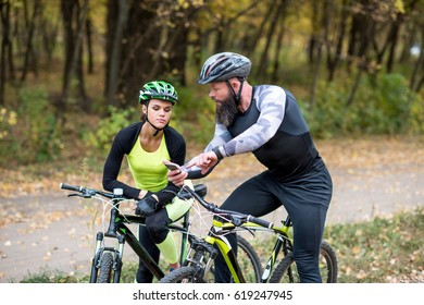 Bearded man showing smartphone to young girl while standing with bicycles in autumn park