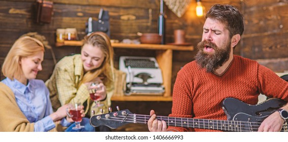 Bearded man singing heart-warming love song. Man with hipster beard playing moving melody on guitar. Musician entertaining wife and daughter. Girls drinking tea or fruit punch and enjoying music.