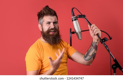Bearded man singing with microphone. Brutal bearded guy singer with microphone on stage. Male lead vocalist singing in recording studio. Vocalist singing in condenser microphone. Concert&music concept