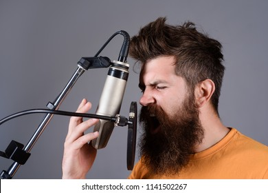Bearded man singing with microphone. Concert&music concept. Brutal bearded guy singer with microphone on stage. Male lead vocalist singing in recording studio. Vocalist singing in condenser microphone