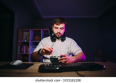 Bearded man sits in a room at home behind a computer workplace and eats noodles with chopsticks in a room with purple light.