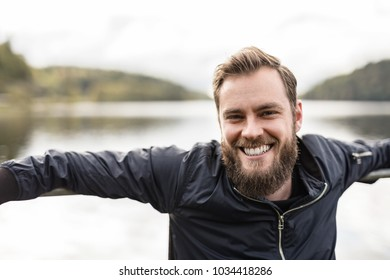 Bearded man sitting down outdoors in front of a lake on a moody day. Wearing a blue jacket looking at camera.