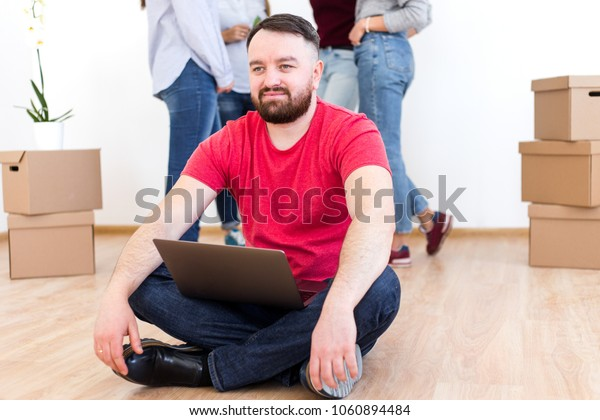 Bearded man sitting with laptop on the floor of a new house on the background of four girls