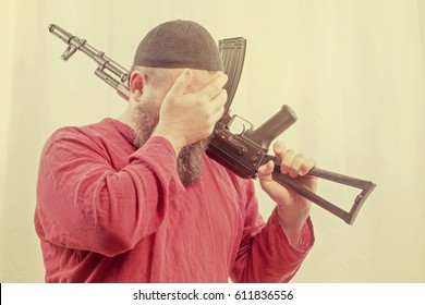 A bearded man in a skullcap and red shirt holding a gun on his shoulder and covers his face with his hand. Toned