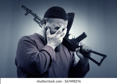 A bearded man in a skullcap and shirt holding a gun on his shoulder and covers his face with his hand. Toned