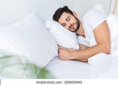bearded man sleeping on bed in bedroom