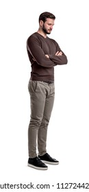 A bearded man in smart casual clothes stands in half-turn with arms folded and looks down. Sad and depressed. Ready to face trouble. Thinking about problems.