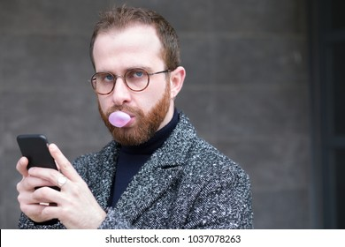 Bearded Man with Smartphone Blowing a Bubble with Bubblegum