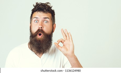 Bearded man smile with hand gesture outdoor. Businessman smiling with beard and and mustache on unshaven face. Happy guy show ok sign on whit backgraund. Agreement and approval, copy space.