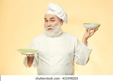 Bearded man smiling and holding plates in studio on yellow background