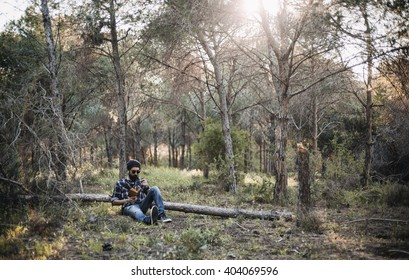 Bearded man smokes a pipe in the wood while reading