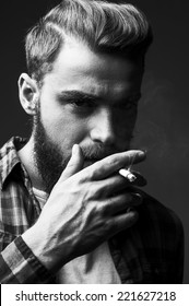 Bearded man smoking. Black and white portrait of handsome young bearded man smoking a cigarette and looking at camera while standing against grey background
