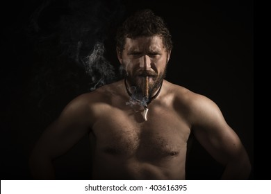 Bearded man smoking cigar in studio