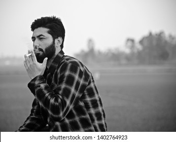 Bearded man smoking a cigarette sitting in a place unique photo