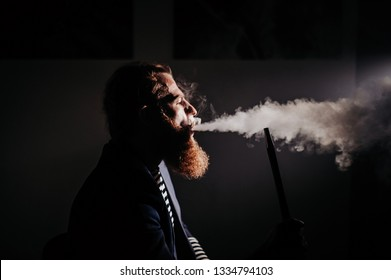 bearded man smoking a hookah in a dark room. hookah lifestyle and smoking concept. portrait of a sailor with a hookah