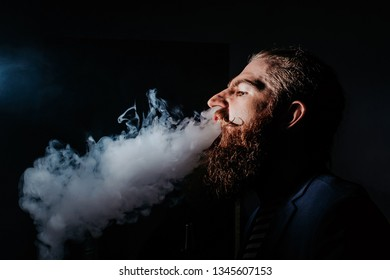 bearded man smoking a hookah in a dark room. hookah lifestyle and smoking concept. portrait of a sailor with a hookah close up