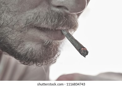 A bearded man smoking a medical marijuana joint