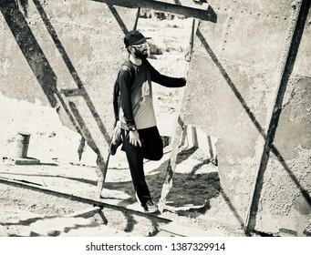 Bearded man standing around an old abandoned metallic door