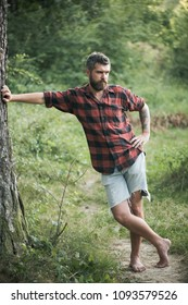 Bearded man standing on path. Hipster hiking in woods. Benefits of walking barefoot. Health and fitness concept.