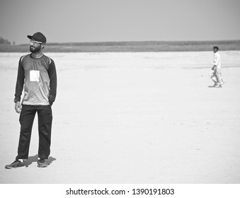 A bearded man standing on a sandy surface in a coastal area