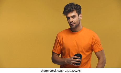 bearded man standing with paper cup isolated on yellow