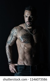 Bearded man with strong torso. Man with tattooed arm and chest. Tattoo model with sexy belly. Sportsman or athlete in fashion jeans. Bodycare or fitness and sport in vintage filter.