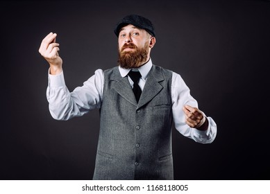 A bearded man in suit talking and gesticulating like italian on black background
