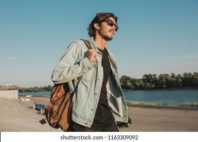bearded man with sunglasses in his hands smiling in the sunset in the summer