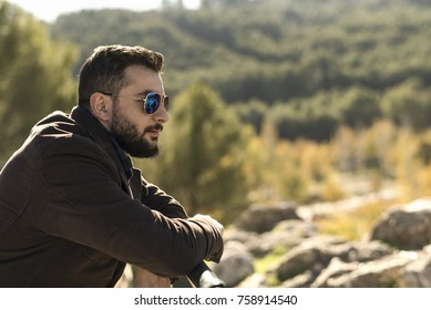 Bearded man with sunglasses supported on a railing looking tonature countryside copyspace in outdoors image