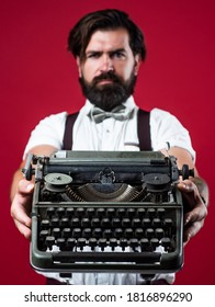 bearded man in suspenders with retro typewriter. brutal guy in bow tie. elegant male typist. handsome hipster use technology in modern life. mature reporter or journalist.