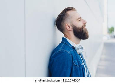 Bearded man taking a quiet moment to relax and de-stress leaning against a receding exterior white wall with eyes closed