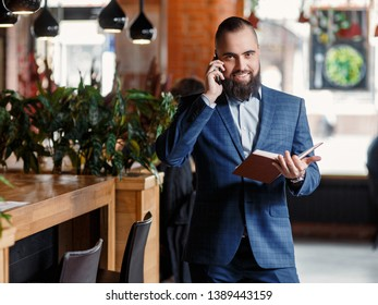 bearded man talking on the phone. businessman talks with notebooks in hands