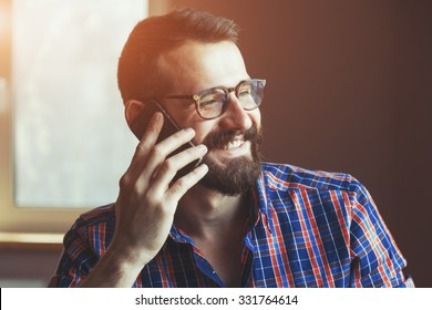 bearded man talking on phone and smiling