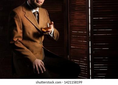 Bearded man taste alchohol drink in luxury interior