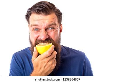 Bearded man tasting a lemon over white background