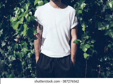 Bearded man with tattoo wearing blank white tshirt.Green garden wall background. Horizontal mockup